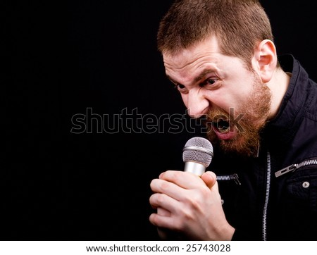 Scream of male angry rocker at the microphone with copyspace - stock photo
