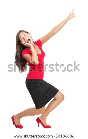 Screaming and pointing woman. Funny full length image of a beautiful mixed race caucasian / chinese young woman model dressed casual in red. Isolated on white background. - stock photo