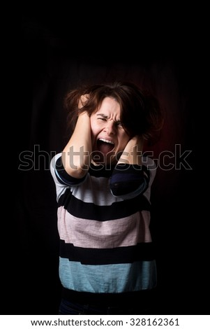 Screaming angry woman pulls her hair. Black dark background. - stock photo