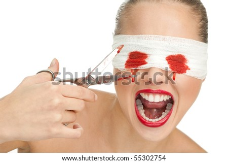 Screaming blind terrified woman with blood and bandage on her eyes and sharp scissors