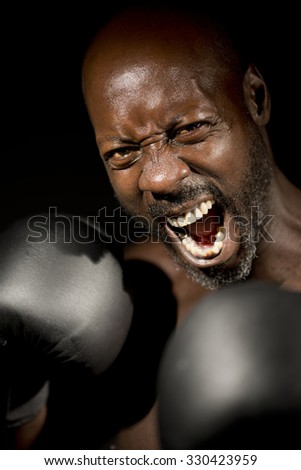 Screaming Boxer Throwing a Punch - stock photo