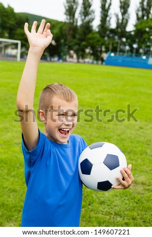 Screaming boy with the ball playing soccer. - stock photo