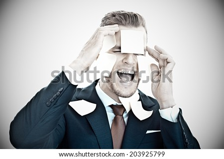 Screaming businessman completely overwhelmed by office work,- Post-It stickers all over his face - stock photo