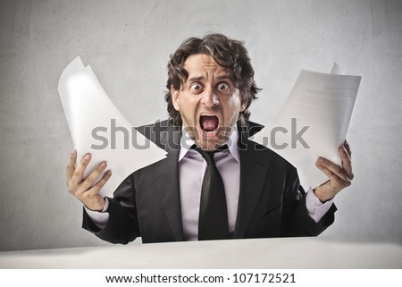 Screaming businessman holding some documents - stock photo