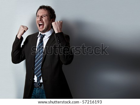 screaming businessman standing in front of a wall - stock photo