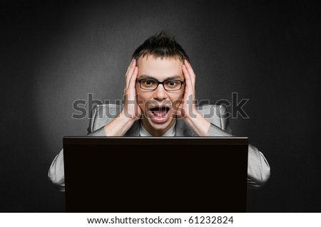 screaming businessman with laptop on black background - stock photo