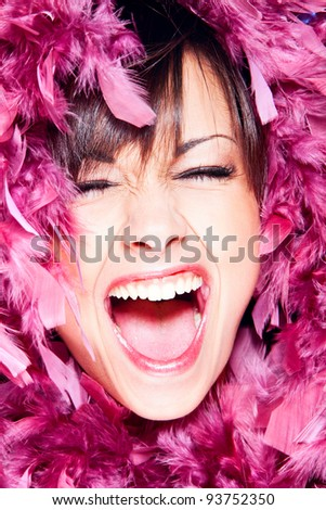 screaming cheerful woman in pink feathers portrait, studio shot - stock photo
