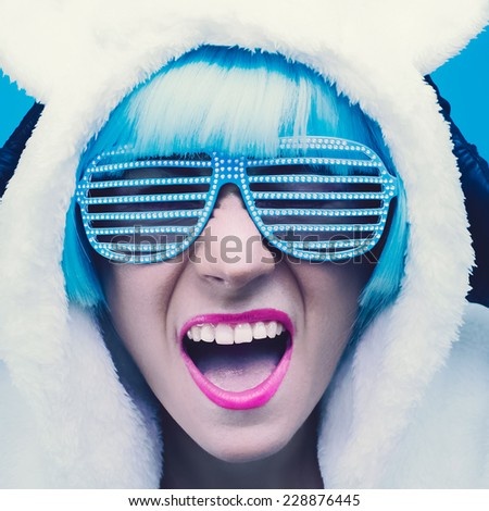 Screaming crazy Girl in hoodie  Bear on a blue background. - stock photo