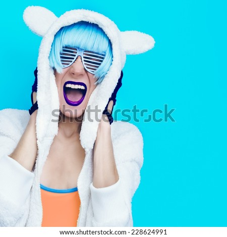 Screaming crazy Girl in hoodie Teddy Bear on a blue background. - stock photo