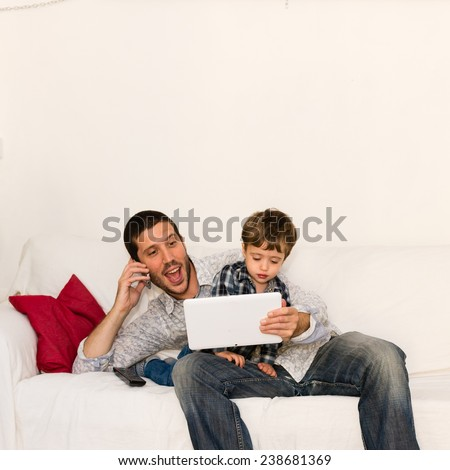 Screaming father making a phone call and playing with tablet with his son sitting on his knees - stock photo