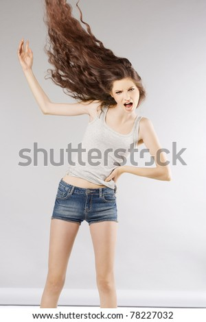 screaming girl with fashion long curly hair looking in camera with angry - stock photo