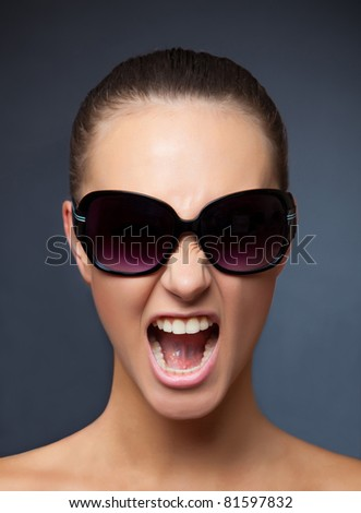 Screaming girl with sunglasses, vertical studio isolated shot - stock photo