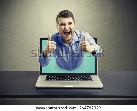 screaming happy man got out of the laptop and showing thumbs up against dark background - stock photo