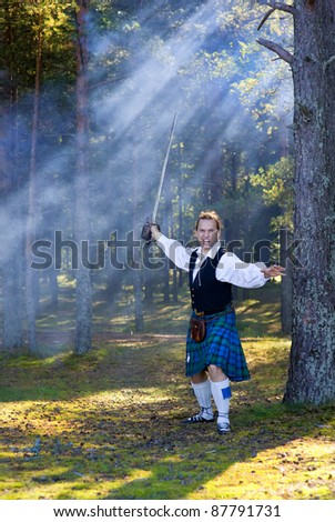 Screaming man in Scottish costume with sword in the forest - stock photo