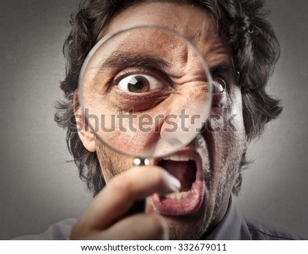 Screaming man looking through a magnifying glass - stock photo