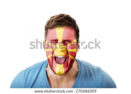 Screaming man with Macedonia flag painted on face. - stock photo