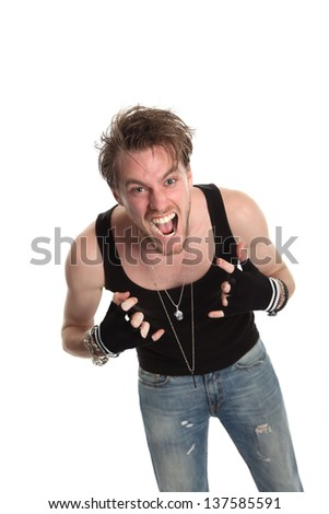 Screaming rocker doing the heavy metal sign. Wearing a black tank top, torn jeans and a skull pendant. Gloves. White background. - stock photo