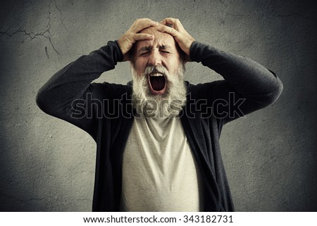 screaming senior man with closed eyes holding his head by hands over grey background