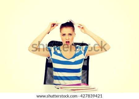 Screaming teenage woman with notebook on head - stock photo