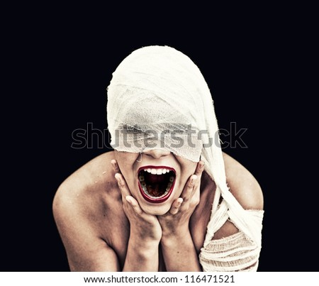 screaming woman  in bandage over black background (gothic style concept) - stock photo
