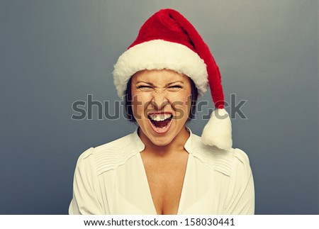 screaming woman in red christmas hat over grey background