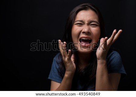 Screaming woman on black background