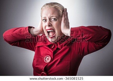 Screaming woman. Shouting woman. Covers her ears with her hands. - stock photo