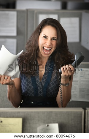 Screaming woman with phone and notes in office cubicle - stock photo