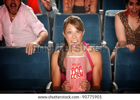 Screaming woman with popcorn bag in theater - stock photo