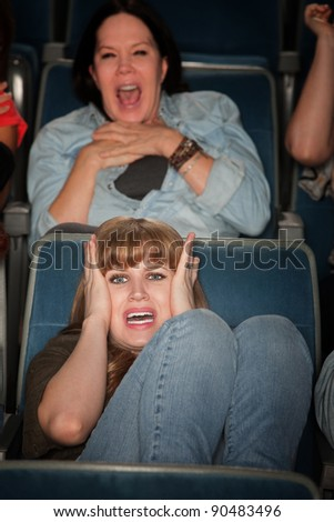 Screaming women watch scary movie in theater - stock photo