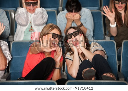 Screaming women with 3D glasses cower in chairs - stock photo