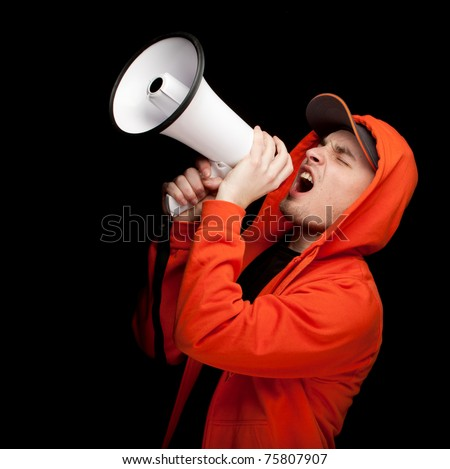 screaming young man in orange sweatshirt with megaphone, black background - stock photo