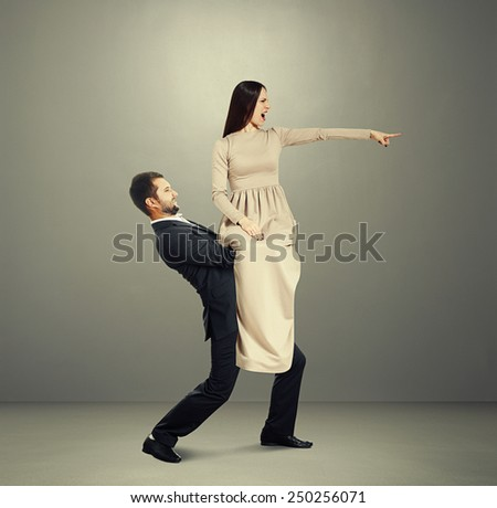 screaming young woman sitting on a man and pointing at something over dark background - stock photo