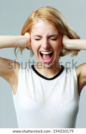 Screaming young woman with closed ears on gray background - stock photo