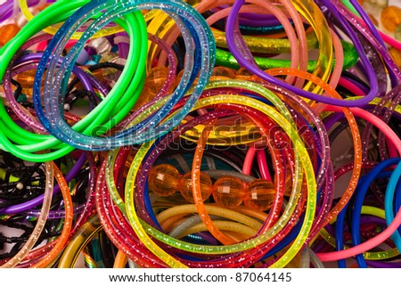 Screen filled with a pile of colored and sparkly bracelets - stock photo
