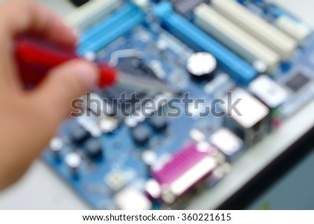 screw driver in hand repairing motherboard blurred background