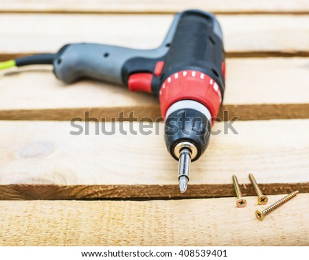 screw gun or electric screwdriver on wooden background with screw, Cordless drilling screwdriver machine  - stock photo
