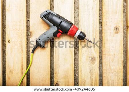 screw gun or electric screwdriver on wooden background with screw, Cordless drilling screwdriver machine, repairing, repair - stock photo