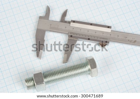 Screw, Nuts and caliper on  graph paper background - stock photo