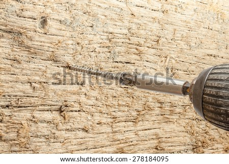 screw with a cordless drill, into a wooden board - stock photo