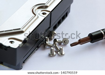 Screwdriver and screws near hard drive on white table - stock photo