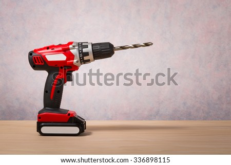 Screwdriver, Cordless Drill on wood table - stock photo