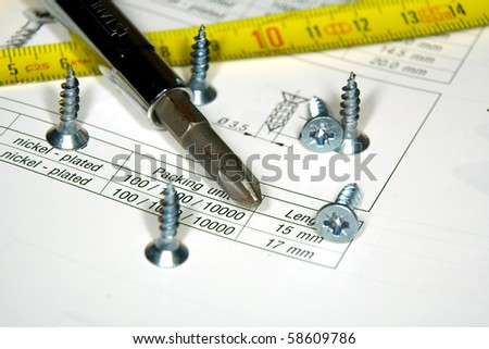 Screwdriver, screws and the drawing on a work desktop
