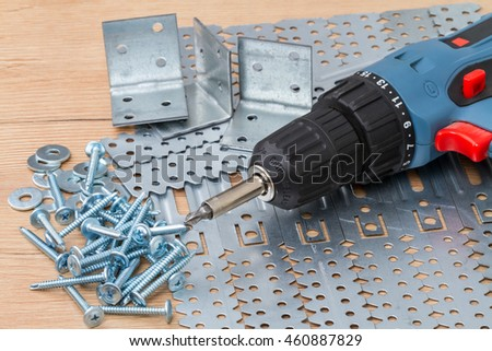 Screwdriver with a bunch of galvanized screws and parts