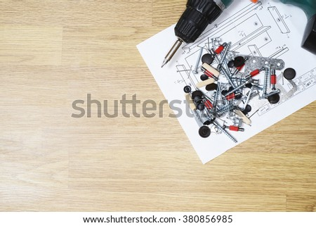 Screwdriver with screws, instruction and furniture parts on light wooden floor. top view. copy space - stock photo