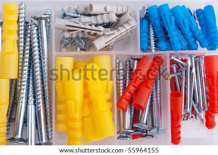 Screws and colored plugs in plastic toolbox, top view