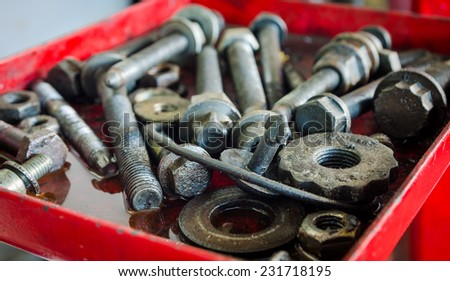 Screws and steel parts and pieces in an oil puddle suggesting dirty industrial vehicle repair services - stock photo