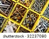 Screws, bolts, nuts and other carpenter stuff in a yellow plastic toolbox (hardware organizer) - stock photo