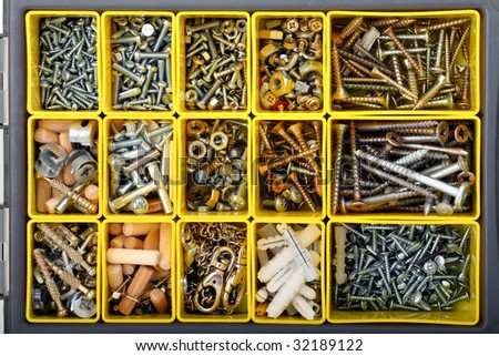 Screws, bolts, wall plugs, nuts and other carpenter stuff in a yellow plastic toolbox, top view - stock photo