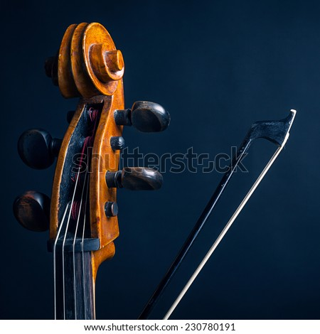 Scroll cello and fiddlestick on dark background - stock photo